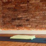 Stilleben aus Yogamatte, Hilfsmitteln, Kerze und Blumen